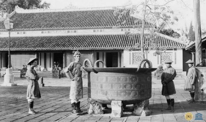 Huế 1920, một võ quan và binh lính đứng cạnh vạc đồng đúc thời chúa Nguyễn đặt trong sân điện Cần Chánh